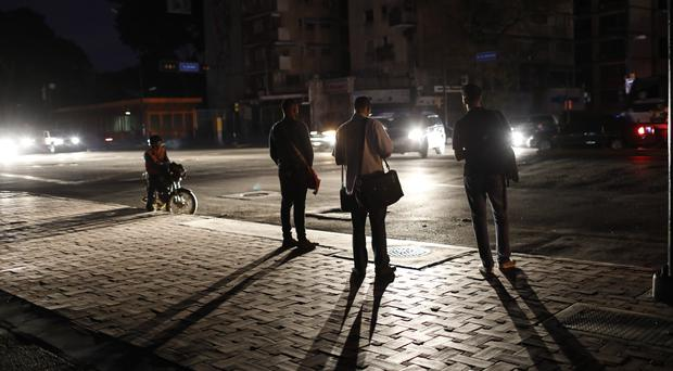 People wait for public transportation during a blackout in Caracas (Ariana Cubillos/AP)