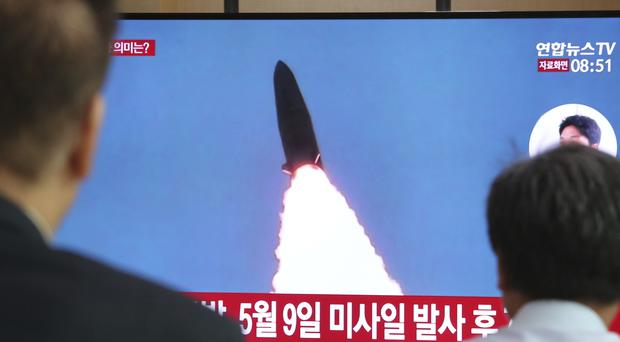People watch a TV showing a file image of North Korea's missile launch (Ahn Young-joon/AP)