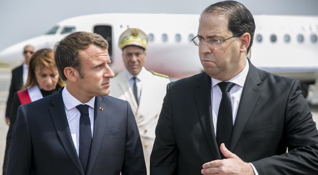 Tunisian Prime Minister Youssef Chahed (right) welcomes French President Emmanuel Macron, upon his arrival at Tunis Carthage airport (Hassene Dridi/AP/PA)