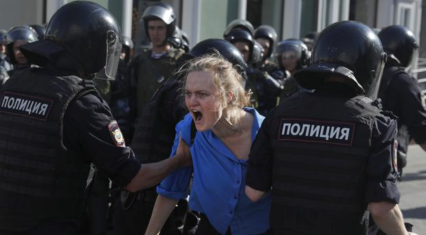 Police officers detain a woman during an unsanctioned rally in the centre of Moscow (Pavel Golovkin/AP)