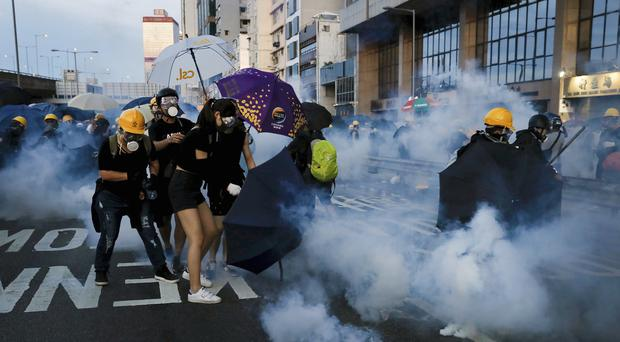 Protesters react from tear gas as they face off with riot policemen on a street in Hong Kong (Vincent Yu/AP)