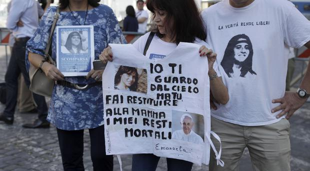 A woman, who says she is a friend of the Orlandi family, holds a T-shirt with pictures of Emanuela Orlandi and Pope Francis (Gregorio Borgia/AP)