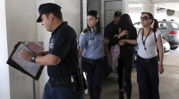 Police officers escort a 19-year-old British woman, second from right, out of Famagusta court (Petros Karadjias/AP)