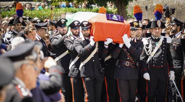 The coffin containing the body of the Carabinieri's officer Mario Cerciello Rega is carried during his funeral in his hometown of Somma Vesuviana, near Naples (Ciro Fusca/AP)