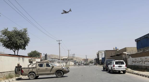 A military aircraft flies over the site of a suicide attack in Kabul (rahmat Gul/AP)
