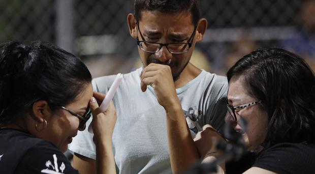 Employees of Walmart cry as they attend a vigil for victims of Saturday's mass shooting in El Paso, Texas (AP)