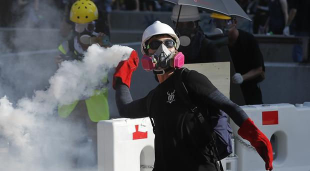 A protester throws back a tear gas canister in Hong Kong (Vincent Thian/AP)