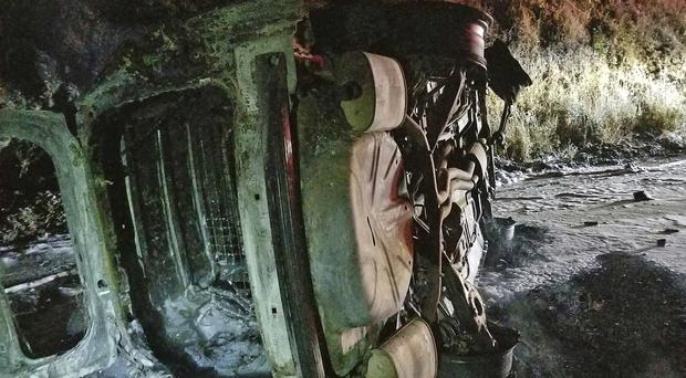 A police car has been destroyed after a bear fell on it in the US, causing the driver to veer into an embankment and the vehicle to burst into flames (Rod Mendes/Hoopa Fire Department/AP)