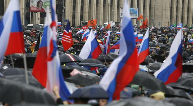People with national flags and various political party flags gather during a protest in Moscow (Alexander Zemlianichenko/AP)
