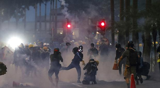 A protester throws a tear gas canister fired by riot policemen in Hong Kong (Vincent Thian/AP)
