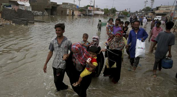 Pakistani families wade through flood road cased by heavy monsoon rains in Karachi, Pakistan, Sunday, Aug. 11, 2019. Monsoon rains have inundated much of Pakistan (Fareed Khan/AP)