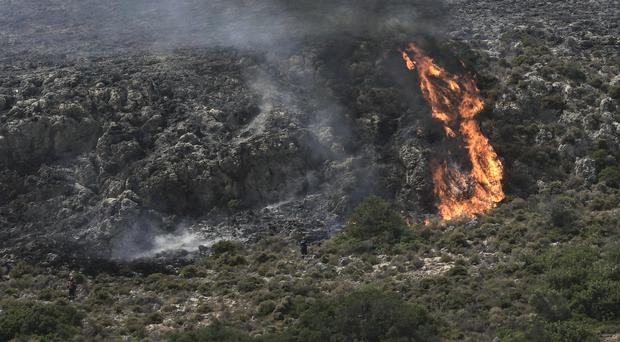 Firefighters approach a wildfire at Elafonisos island (Nikolia Apostolou/AP)