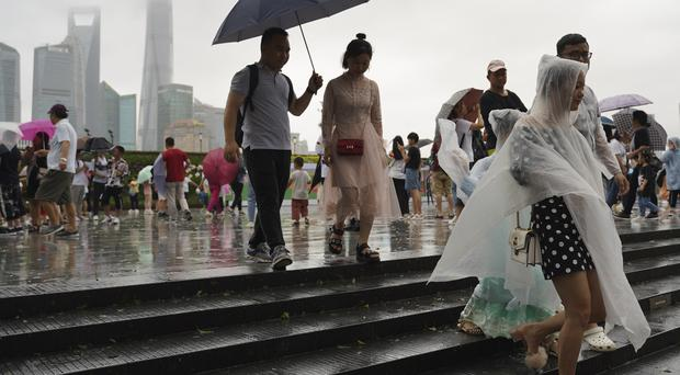 Visitors leave from the bund as Typhoon Lekima approaches in Shanghai (Erika Kinetz/AP)
