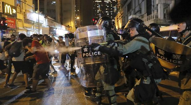 Riot police use pepper spray against protesters (Kin Cheung/AP)
