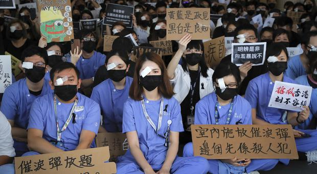 Medical staff stage a protest against police brutality (Kin Cheung/AP)