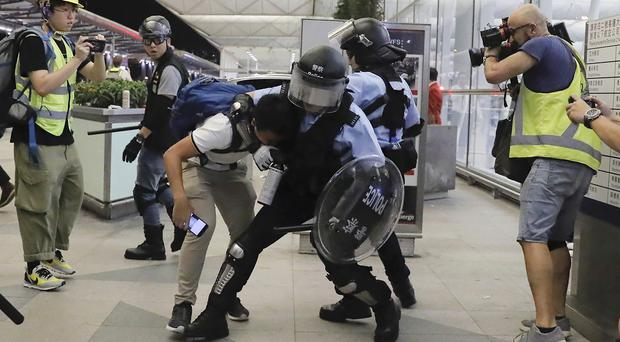 Policemen in riot gear arrest a protester (Kin Cheung/AP)