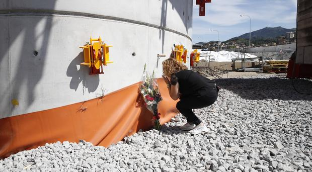 A relative of one of the victims leaves flowers on a pillar of the new bridge (Antonio Calanni/AP)