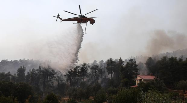 An helicopter operates over a wildfire in Makrymalli village on the Greek island of Evia (Yorgos Karahalis/AP)