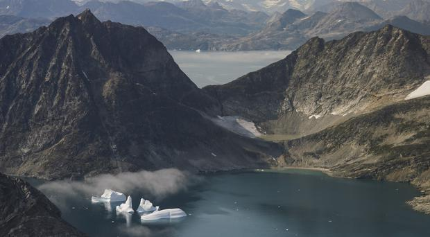 Icebergs are photographed from the window of an airplane carrying Nasa scientists as they fly on a mission to track melting ice in eastern Greenland (Mstyslav Chernov/AP)