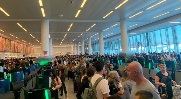 Travellers stand in long lines to clear customs at JFK International Airport (Brenna but in Leo Season via AP)