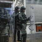 Police officers armed with riot gears stand guard (Vincent Thian/AP)
