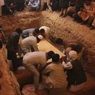 Afghans bury the bodies of victims of the Dubai City wedding hall bombing during a mass funeral in Kabul (Rafiq Maqbool/AP)