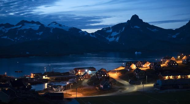 Homes are illuminated after the sunset in Tasiilaq, Greenland (Felipe Diana/AP)
