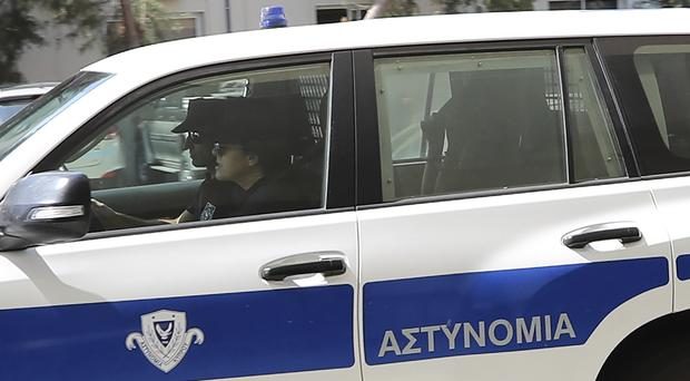 A 19-year old British woman, is seen in the rear seat of a police vehicle, with head covered, as she leaves the Famagusta court in Paralimni, Cyprus (Petros Karadjias/AP)