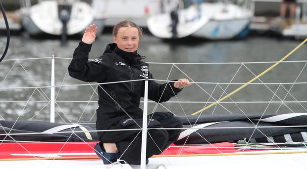 Greta Thunberg waves on arrival in New York (Mary Altaffer/AP)