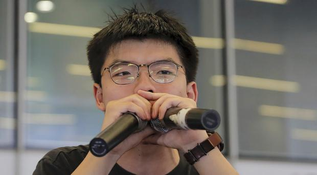 Joshua Wong speaks to protesters near the Legislative Council following a massive protest against the unpopular extradition bill in Hong Kong (AP Photo/Kin Cheung, File)