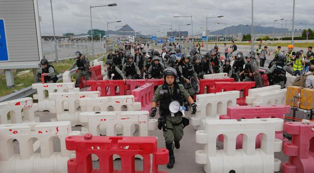 Police remove road barriers put up by protesters near the airport in Hong Kong (Kin Cheung/AP)