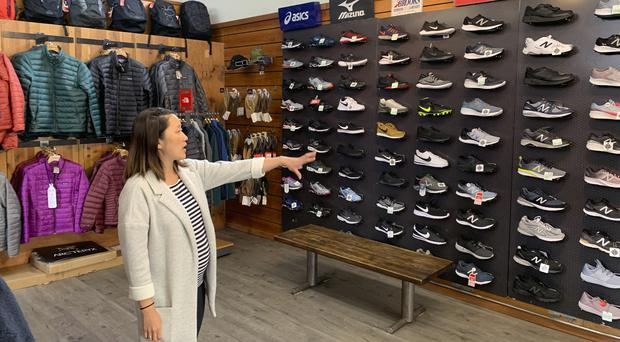 Jennifer Lee, whose family owns a shoe store in San Francisco, with some fo the goods imported from China (Terry Chea/AP)