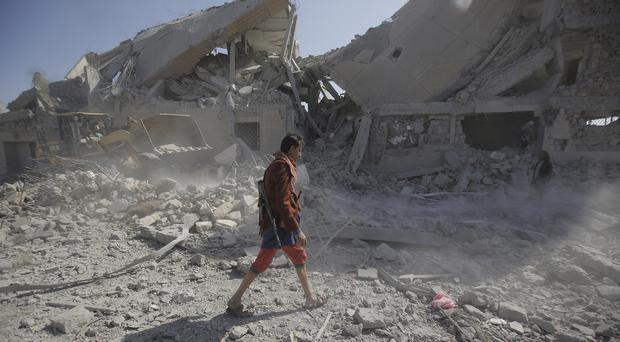 A Yemeni man walks amid the rubble of a Houthi detention centre destroyed by Saudi-led air strikes (Hani Mohammed/AP)