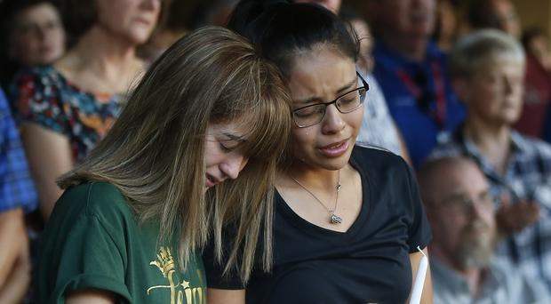 High school students Celeste Lujan and Yasmin Natera mourn their friend Leila Hernandez, one of the victims of the Saturday shooting in Odessa (AP)
