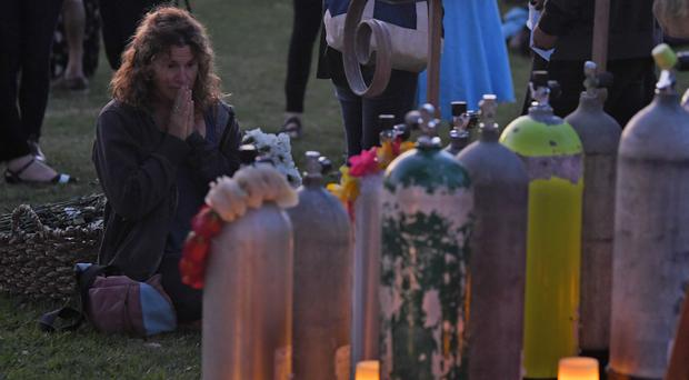 An attendee kneels in front of scuba tanks that were placed to represent each victim during a vigil (Mark J Terrill/AP)