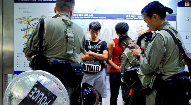 Riot police check passengers' bags at airport express central station in downtown Hong Kong (Vincent Yu/AP)