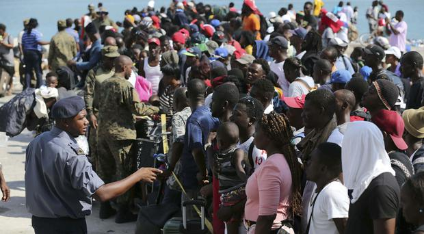 An army officer speaks with people before they board a ferry to Nassau (Fernando Llano/AP)