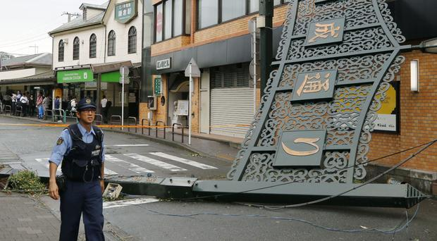 A police officer walks past a fallen signboard hit by typhoon at a shopping district in Kamakura, near Tokyo (Kyodo News/AP)
