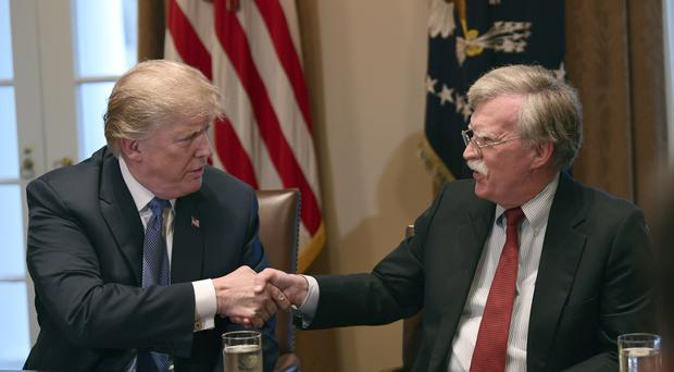 President Donald Trump, left, shakes hands with then national security adviser John Bolton (Susan Walsh/AP)