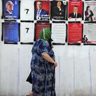 A woman pauses as she walks past candidates' posters (Hassene Dridi/AP)