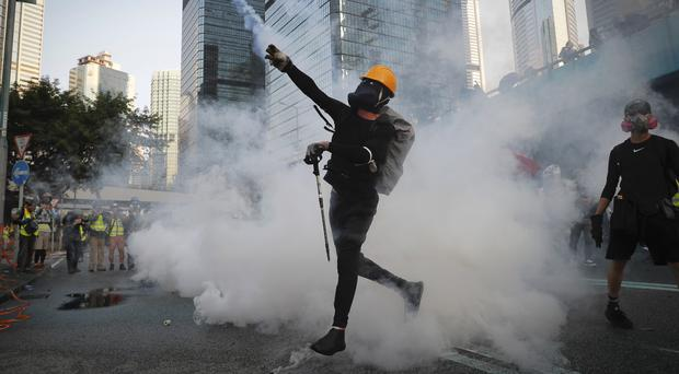 An anti-government protester throws back a tear gas canister fired by the police during a demonstration near Central Government Complex in Hong Kong, Sunday, Sept. 15, 2019. Police fired a water cannon and tear gas at protesters who lobbed Molotov cocktails outside the Hong Kong government office complex Sunday, as violence flared anew after thousands of pro-democracy supporters marched through downtown in defiance of a police ban (Kin Cheung/AP)