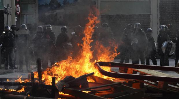 Police face a burning barricade during protests (AP)