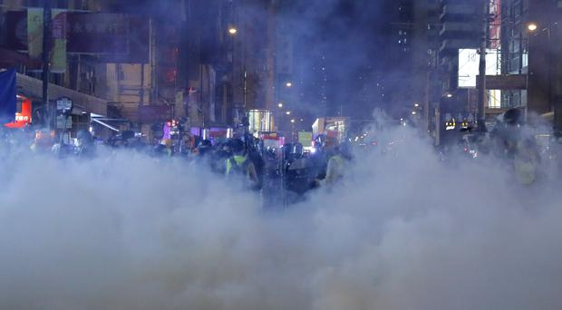 Tear gas fills the street as protesters continue to battle with police on the streets of Hong Kong (Kin Cheung/AP)