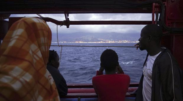 Migrants look at the Italian shoreline from aboard the Ocean Viking as it approaches the Sicilian port of Messina (Renata Brito/AP)