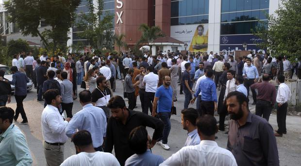 People stand outside their office after an earthquake is felt in Islamabad (AP Photo/Anjum Naveed)