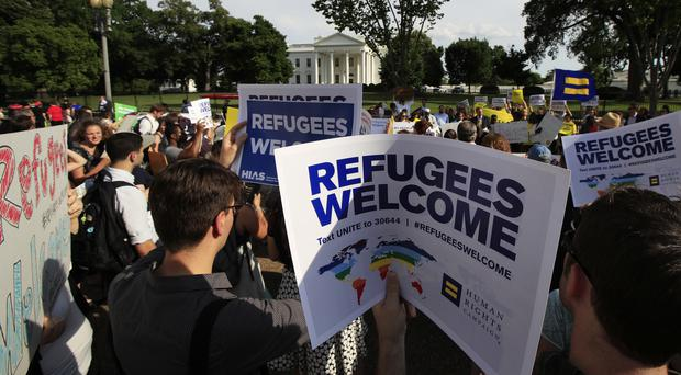 Refugees and community activists gather in front of the White House in Washington (Manuel Balce Ceneta/AP)