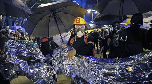 Anti-government protesters hold aluminium foil to protect them from the police's blue-coloured water cannon (Kin Cheung/AP)