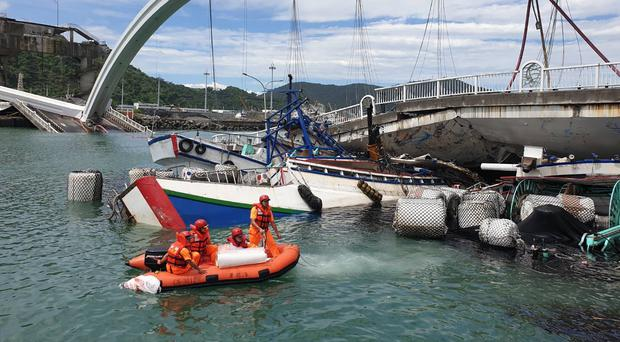 Rescuers work near the site of the collapsed bridge (Taiwan's Coast Guard/AP)