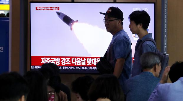People pass by a TV showing a file image of North Korea's missile launch (Ahn Young-joon/AP)
