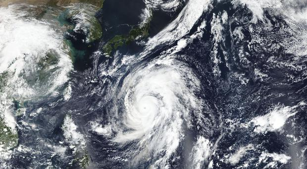 A photo taken by Nasa-NOAA's Suomi NPP satellite shows Typhoon Hagibis approaching Japan, top (EOSDIS) via AP)